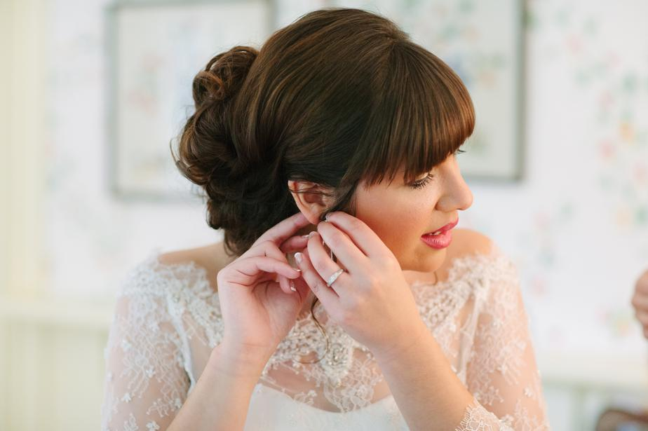 bride putting on earing for gibbet hill wedding